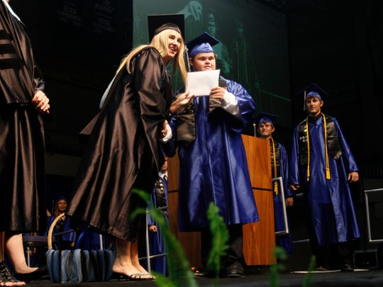 Ida S. Baker High School Assistant Principal of Curriculum Debbie Diggs hands her son, Christian his diploma while twin sons Drayton and Jordan , right, wait in the wings Saturday at Alico Arena.