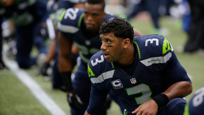 Seattle Seahawks quarterback Russell Wilson stretches on the field before an NFL football game against the Carolina Panthers, Sunday, Oct. 18, 2015, in Seattle.