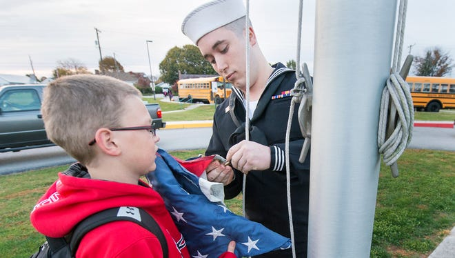 Austin Tyler, age 10, left, is assisted in his daily flag raising duty by his brother Chris Gray during a surprise visit to Park Hills Elementary School in Penn Township Monday October 26, 2015. Gray is currently serving in the Navy aboard the USS Anzio.
