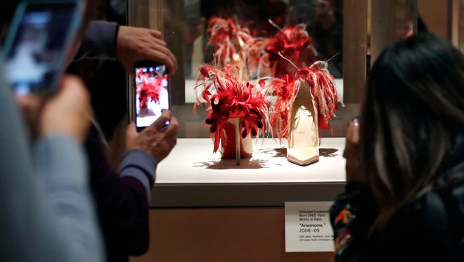 "In this Tuesday, Nov. 15, 2016 photo, guests snap photographs of a pair of high heels, decorated with red frilled details, are displayed at the Peabody Essex Museum in Salem, Mass. From flats to stilettos, what we put on our feet says something about who we are. That's the premise of new exhibition in Massachusetts. ""Shoes: Pleasure and Pain"" opens Saturday, Nov. 19, 2016, at the Peabody Essex Museum in Salem."