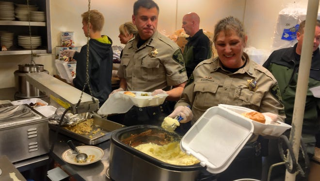 Marion County Sheriff Jason Myers (center) and his deputies were among the scores of volunteers helping out at the Covered Bridge Cafe during Stayton's 10th Annual Community Dinner.