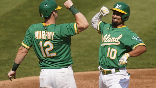 Oakland Athletics' Marcus Semien (10) celebrates after hitting a two-run home run that scored Sean Murphy (12) against the Chicago White Sox during the second inning of Game 2 of an American League wild-card baseball series Wednesday in Oakland, Calif.