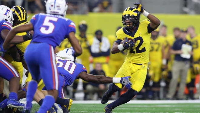 Wolverines running back Chris Evans (12) runs with the ball against the Florida Gators at AT&T Stadium.