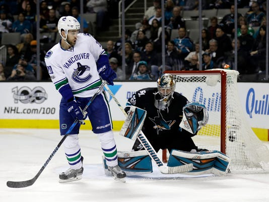 San Jose Sharks goalie Aaron Dell, right, stops a shot next to Vancouver Canucks center Brandon Sutter during the second period of an NHL hockey game Thursday, March 2, 2017, in San Jose, Calif. (AP Photo/Marcio Jose Sanchez)