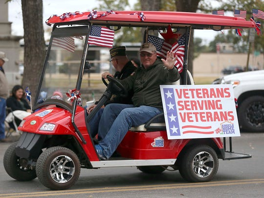 Veterans wave to spectators during the 14th annual