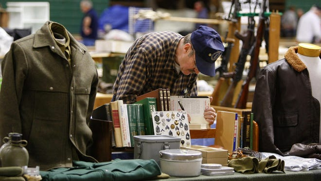 Larry Dobb, who sells military collectibles, writes a price in a book at the Great Falls Gun and Antique Show.