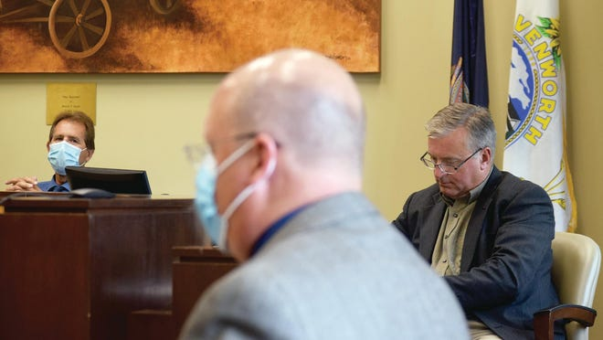 Leavenworth County Commission Chairman Doug Smith, left, wears a mask Wednesday during a commission meeting. Commissioner Mike Stieben, right, started the meeting with a mask but eventually removed it. Also pictured is County Administrator Mark Loughry, center. Commissioners plan to meet this evening to discuss an order from Gov. Laura Kelly that requires people to wear masks in public spaces.