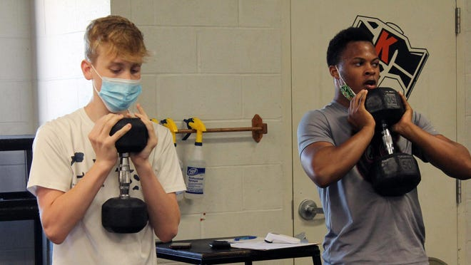 Jack Coombes and Marquez Logan work out with free weights at the Goods Gym weight room at Kewanee High School.