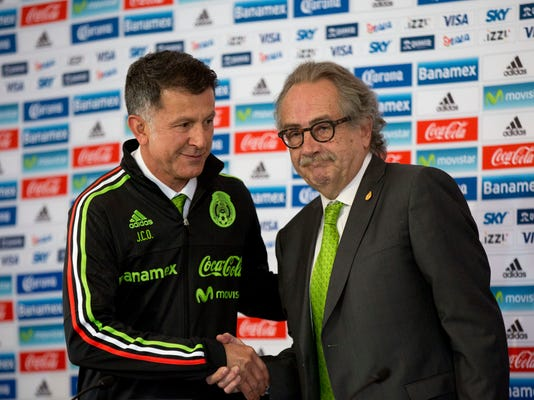 Juan Carlos Osorio, left, newly-appointed head coach of Mexico's national soccer team, shakes hands with Mexico's Football Federation President Decio de Maria after receiving his team jacket, during a press conference in Mexico City, Wednesday, Oct. 14, 2015. (AP Photo/Rebecca Blackwell)