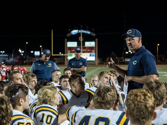 Castle Head Coach Doug Hurt congratulates his team on their win over the Harrison Warriors at Romain Stadium last fall.