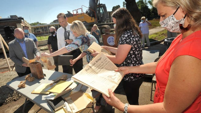 Weymouth School Committee Chairperson Lisa Belmarsh looks at an April 3, 1963 edition of The Patriot Ledger found among the items in a time capsule during the groundbreaking of the new Maria Weston Chapman Middle School on Thursday, July 2, 2020.