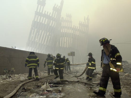 Firefighters work beneath the destroyed mullions, the