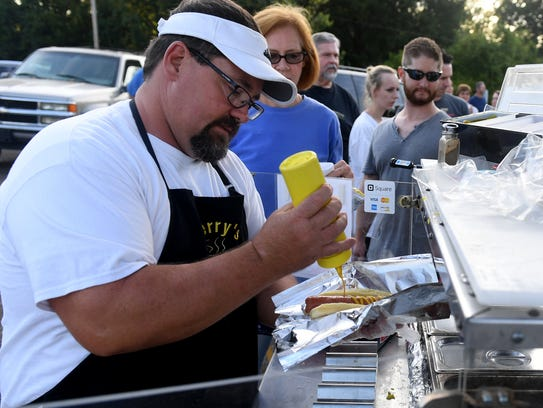 Jeff Perry of Perry's Hot Dog Hut spreads mustard onto