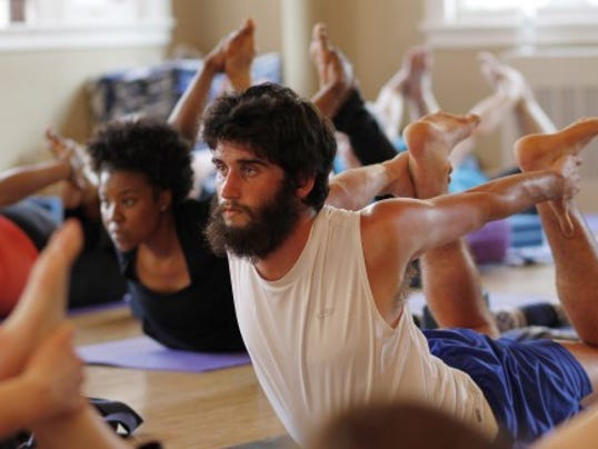 While females dominate most Yoga classes, the exercise is extremely beneficial for guys, too. Check out this article in Men's Fitness. (AP Photo/The Philadelphia Inquirer, Michael S. Wirtz)