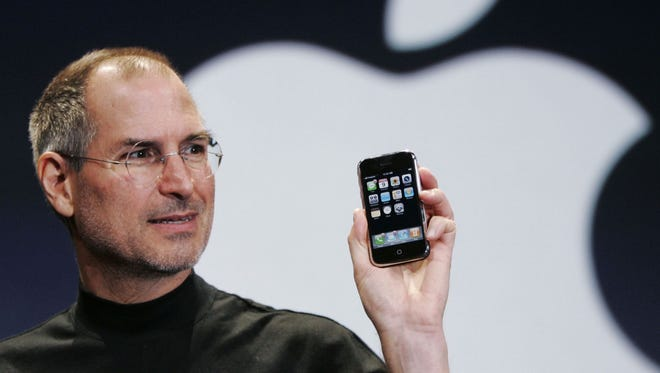 In this Jan. 9, 2007, file photo, Apple CEO Steve Jobs holds up an iPhone at the Macworld Conference in San Francisco.