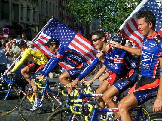 Tour de France winner Lance Armstrong, left, rides down the Champs Elysees in Paris with his teammates Frankie Andreu., George