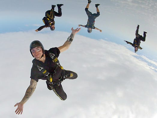 "Sgt. 1st Class Jared Zell, foreground, and other members of the U.S. Army's Golden Knights skydive Wednesday, August 27, 2014, above Frankfort Municipal Airport. Zell is a 2003 graduate of Benton Central High School. This jump was number 6,277 for Zell. ""I can't believe I get paid to do this,""  he said."