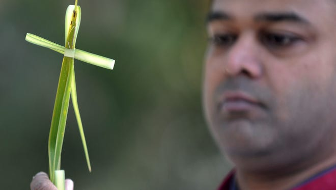 An Indian Christian devotee holds a cross made of palm fronds during a Palm Sunday procession at Wesley Church in Secunderabad, the twin city of Hyderabad on March 20, 2016.
