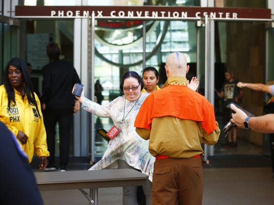 Security uses hand metal detectors to check Phoenix Comicon attendees on May 26, 2017, at the Phoenix Convention Center.