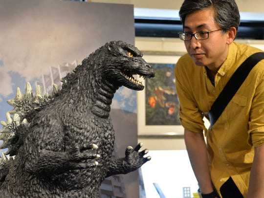 A Godzilla fan looks at a 1-meter tall statue at a Godzilla art exhibition in Tokyo on May 2.