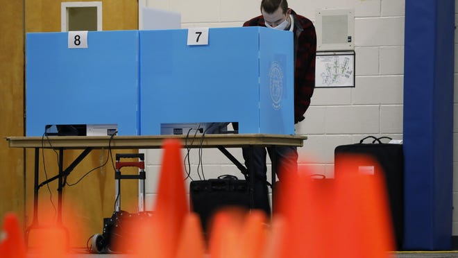 A voter casts his ballot at Whit Davis Elementary School in Athens on Tuesday.