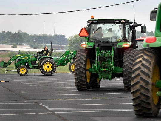Future Famers of America students at Henderson County High park their farm tractors in the school's back parking lot after they were allowed to drive their farm tractors to school as a reward for a third place finish at the Murray State University FFA Field Day Friday, April 28, 2017.