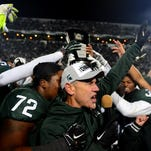"As the team hoists the Big Ten East Division trophy behind him, head coach Mark Dantonio screams out ""Go Green"" as he addresses the crowd after MSU's 55-16 win over Penn State Saturday at Spartan Stadium in East Lansing."