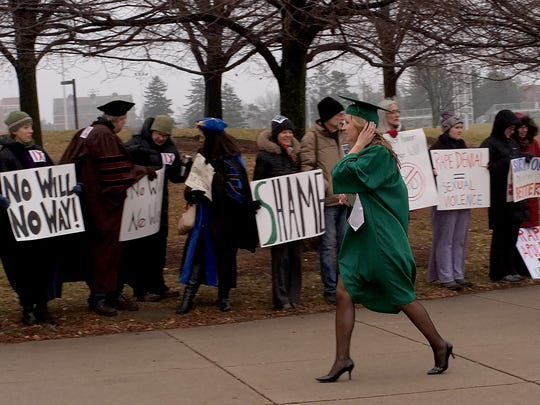 MSU graduating students walk by people protesting the selection of George Will as a keynote speaker at commencement Saturday, December 13, 2014. Will's previous statements about rape victims sparked protests at the commencement.