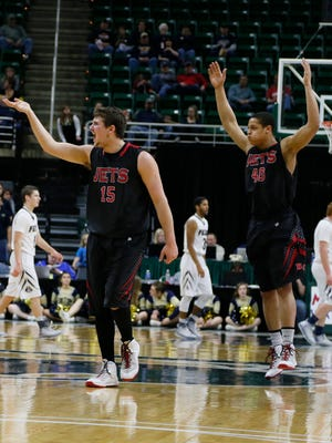 Powers North Central's Robert Granquist Jr., left, and Morgan Cox excite their fans during a timeout in the first half of their game against Fulton-Middleton in MHSAA Boys Class D semi final basketball game on Thursday, March 26, 2015 in East Lansing.