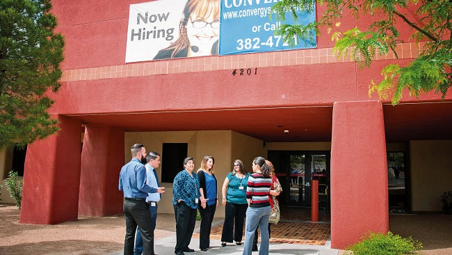 Workers are seen in front of the now-closed Convergys call center in Las Cruces, N.M. in a 2015 file photo.