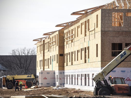 Workers walk past a section of new construction on the 134 Crossing apartment building development Saturday, March 11, in St. Cloud. A new report says while Stearns and Sherburne counties issued more permits to build multifamily units than two-thirds of Minnesota counties, the demand for affordable housing far outpaces supply.