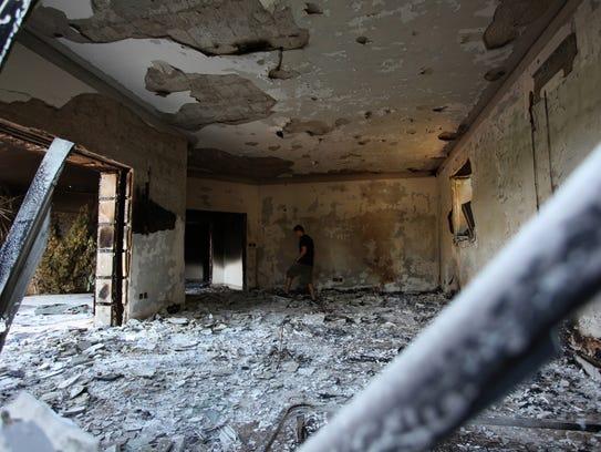 A man walks through the rubble of the U.S. consular