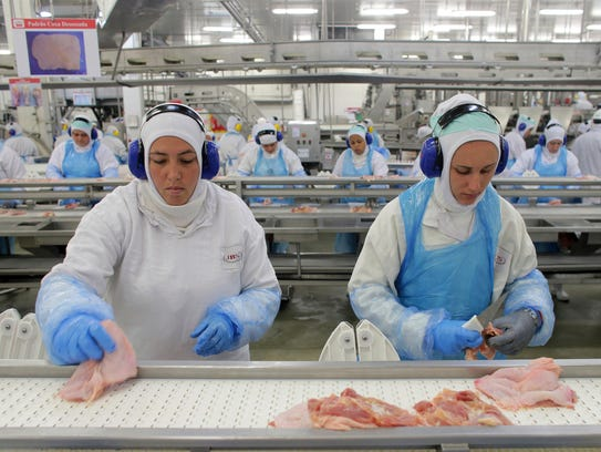 Workers prep poultry at the meatpacking company JBS,