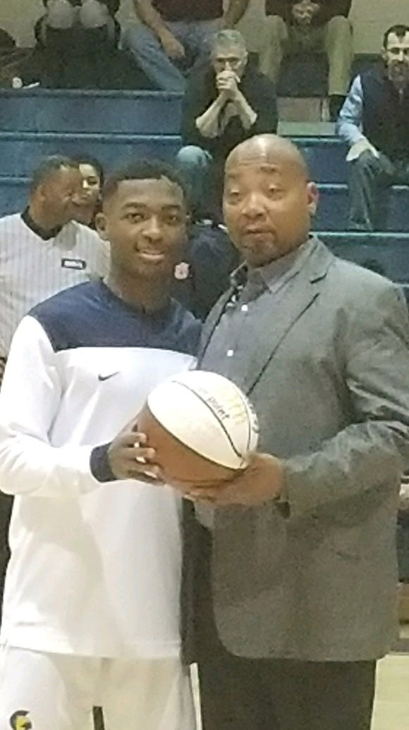 St. James senior guard Damien Madison, left, pictured with Trojans head coach Nigel Card. Madison had 45 points in an overtime win over Trinity on Jan. 12.