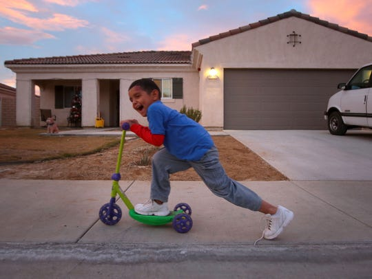 A child plays outside a house in Coachella built under a Coachella Valley Housing Coalition program where homeowners build their own houses on December 21, 2015.