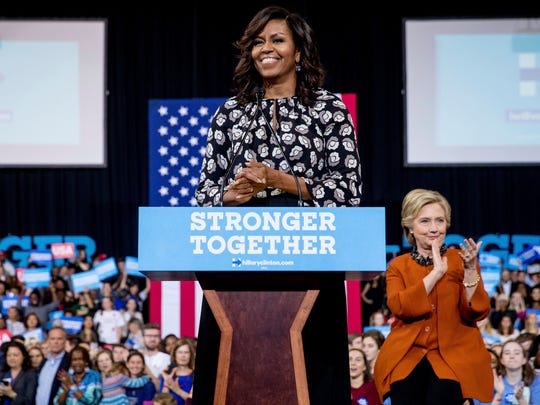 First lady Michelle Obama speaks at a rally for Hillary Clinton in Winston-Salem, N.C., on Oct. 27, 2016, as the Democratic presidential nominee looks on.