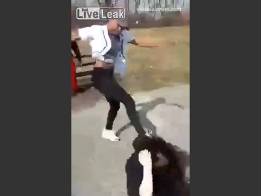 screen grab from a video showing a woman beat down another woman and