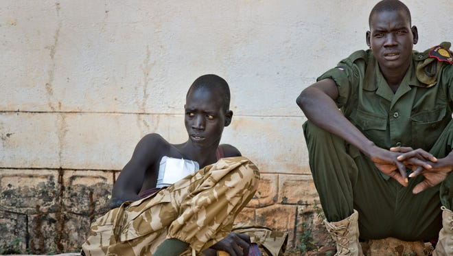 A wounded soldier sits with a colleague in an outside courtyard at the Juba Military Hospital in Juba, South Sudan on Dec. 28, 2013. A spokesman for South Sudan's military says fighting continues in the oil-producing Unity state despite ongoing efforts by regional leaders to get both sides to agree to an immediate cease-fire.