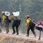 Allison Stahl carries a basket to her car on Aug. 27 as firefighters walk past on their way to establish a hose line in Essex, Mont. The area was evacuated Thursday afternoon in the face of the growing Sheep Fire threatening the community at the edge of Glacier National Park.