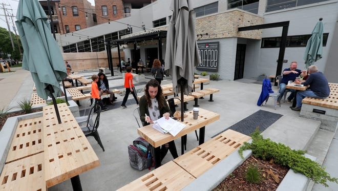 Ariel Powers of Milwaukee studies as she drinks her coffee on the patio at the new Stone Creek Coffee location on N. Downer Ave. at E. Park Place. The plaza-like patio features built-in benches. In the background is sheltered seating that protects from sun or light rain; a four-season room beyond that has garage doors to open on nice days.