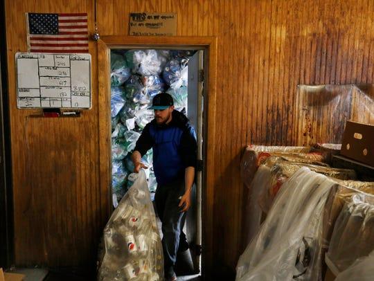 Ben Allen takes out a full bag of soda bottles Thursday,