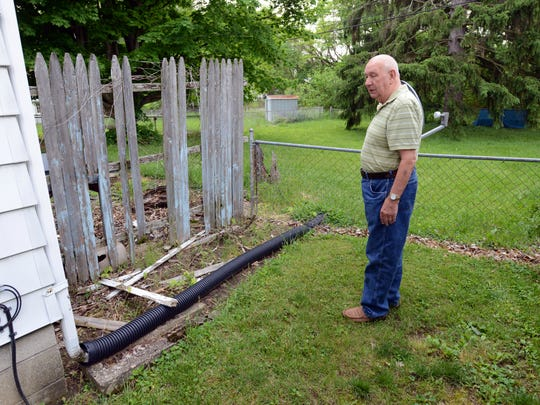 Charles Azbell stands next to the house next to his on Pennsylvania Avenue in Lancaster. The house has been vacant for more than a decade.