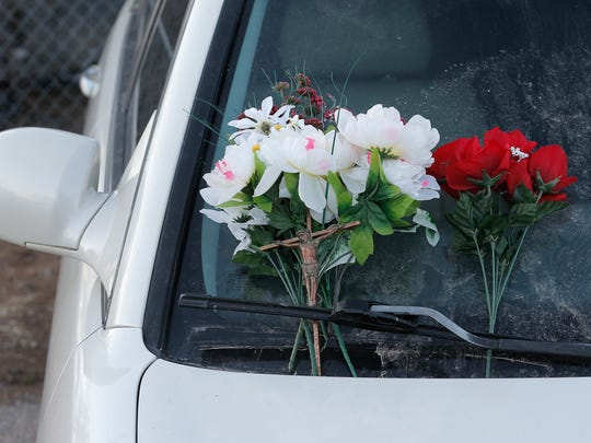 Flowers and a crucifix were placed on the windshield of a car in front of a mobile home that caught fire on Sunday. A man was pulled out of the home and taken to an area hospital, where he was pronounced dead.