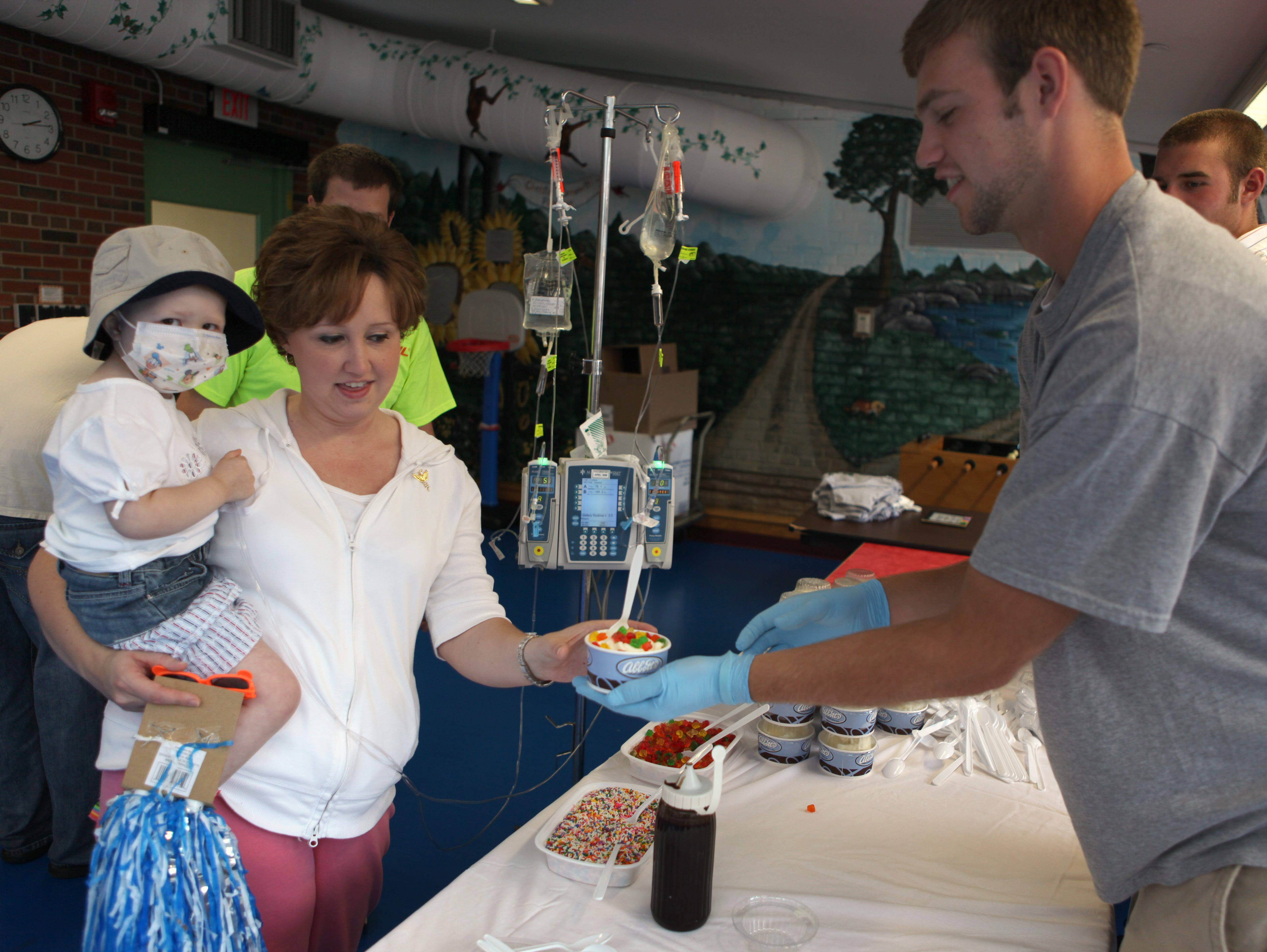 Former Livonia High football player Matt Girolmo, right, serves ice cream to Hailey Coniber, held by her mother Missy Coniber at the Golisano Children's Hospital at Strong before the 2009 Eddie Meath All-Star Game.