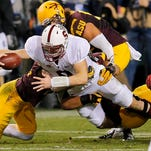 Stanford quarterback Kevin Hogan dives for a first down as he his pulled down by Arizona State defenders during the first half of the Pac-12 Championship game Saturday in Tempe, Ariz.