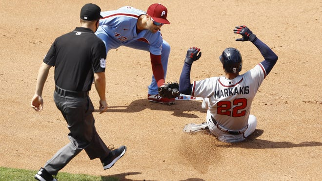 Atlanta Braves' Nick Markakis, right, is tagged out by Philadelphia Phillies second baseman Neil Walker after trying to steal second during the fourth inning of the first baseball game in a doubleheader, Sunday, Aug. 9, 2020, in Philadelphia.