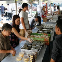 From left.  Traditional Vietnamese food bahn cam (sesame ball), bahn gai (sweet sticky rice cake), and banh u (pyramid glutinous rice cake) is served at the St. Andrew Dung-Lack Festival in Lansing.