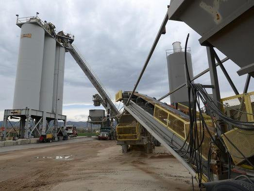 Aggregate at right, travels by conveyor belt to the mixer to be mixed with liquid asphalt then sent to the silos at left, where it is loaded into trucks, at the Martin Marietta Material's asphalt plant in Fort Collins Wednesday April 23, 2014.