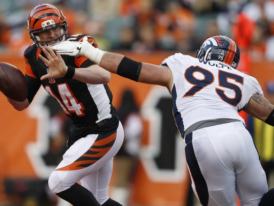Bengals quarterback Andy Dalton (14) is flushed out of the pocket by Denver Broncos defensive end Derek Wolfe (95) in the fourth quarter of their game at Paul Brown Stadium in 2012.