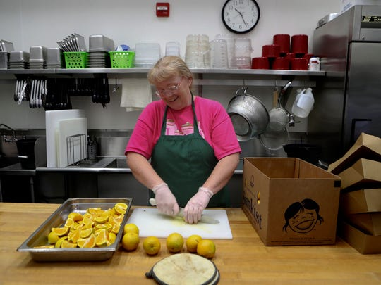 Manzanita School cook Becky Weaver cuts oranges and prepares lunches Wednesday at Cypress School in Redding. The lunches were being prepared for the Seamless Summer Feeding Program.